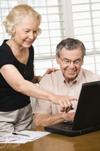 Mature Caucasian couple looking at laptop.